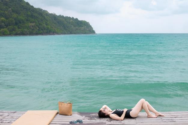 Donna sulla spiaggia tropicale, giovane donna asiatica sdraiata sulla spiaggia di legno del molo.