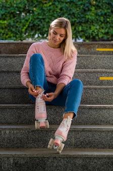 Donna sulle stelle che legano lacci delle scarpe sui pattini di rullo