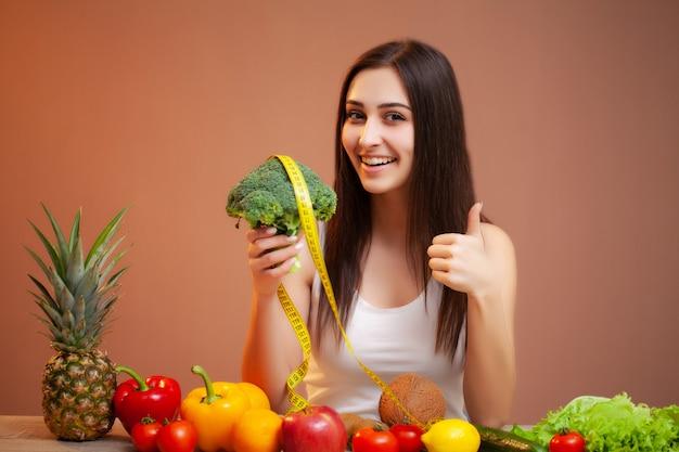 Donna sveglia ad una tabella che tiene i broccoli