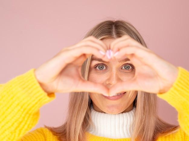 Donna sveglia che mostra gesto del cuore