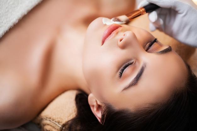 Donna sveglia che ottiene la maschera di protezione della stazione termale nello studio di bellezza