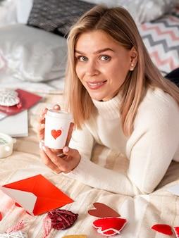 Donna sveglia che propone con la tazza di caffè