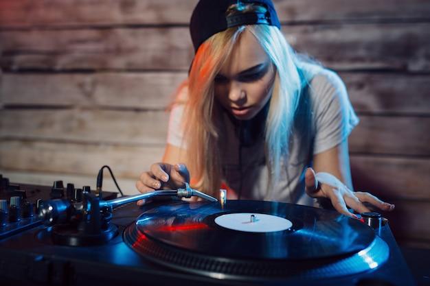 Donna sveglia del dj divertendosi giocando la musica alla festa del club