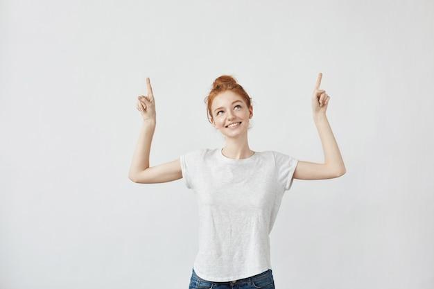 Donna sveglia dello zenzero con le lentiggini che sorride indicando le dita su.