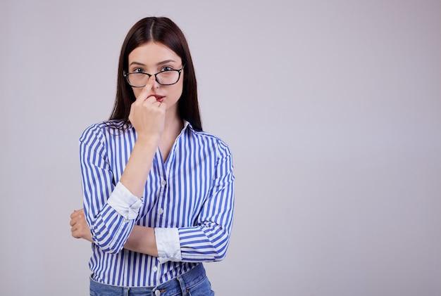 Donna sveglia di affari con capelli castani, posa rosa completa delle labbra. indossa una camicia a righe bianca e blu e occhiali da pc neri.