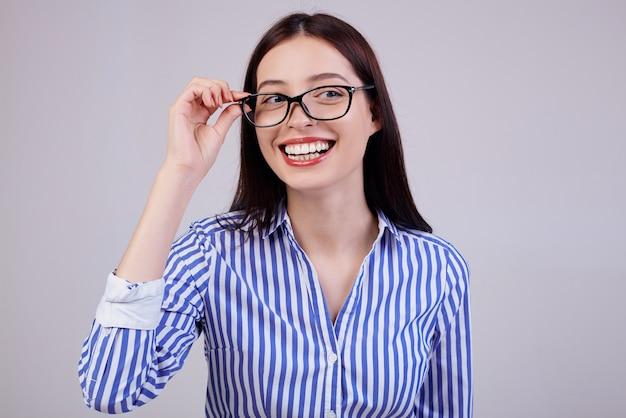 Donna sveglia di affari con capelli castani, posa rosa completa delle labbra. indossa una camicia a righe bianche e blu e occhiali da computer neri. opera. sorriso.
