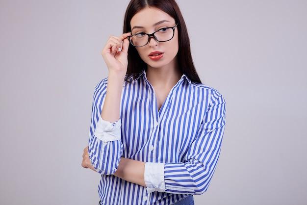 Donna sveglia di affari con capelli castani, posa rosa completa delle labbra. indossa una camicia a strisce bianche e blu e occhiali da computer neri. lavoratore.