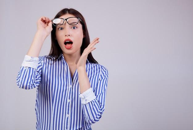 Donna sveglia di affari con capelli castani, posa rosa completa delle labbra. indossa una camicia a strisce bianche e blu e occhiali da computer neri. sorpreso. sembra di lato. copia spazio.