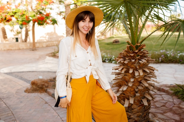 Donna sveglia in cappello di paglia e camicetta bianca in posa in hotel tropicale durante le vacanze.