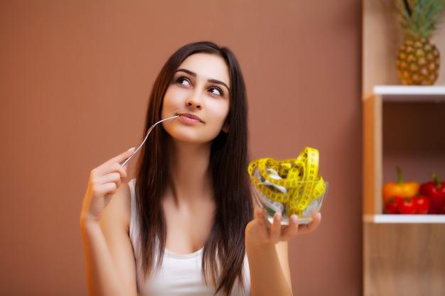 Donna sveglia su una dieta che tiene un piatto pieno di nastro adesivo