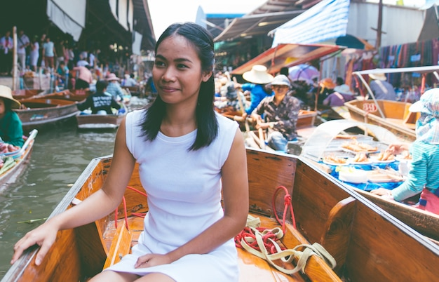Donna tailandese al mercato galleggiante