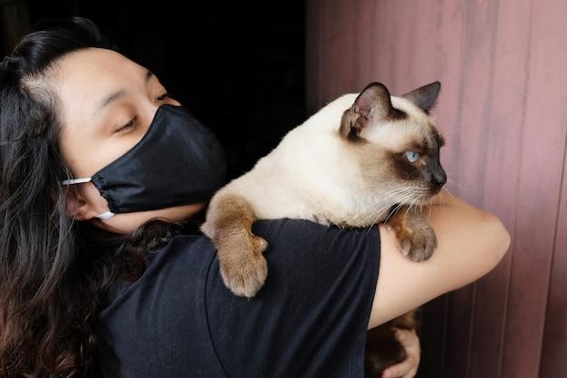 Donna tailandese asiatica che trasporta un gatto siamese e indossa una maschera di stoffa nera per prevenire il virus covid-19 o corona e la malattia epidemica in thailandia e in tutto il mondo. concetto di salute e malattia