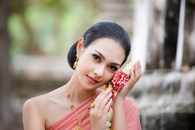 Donna tailandese con il vestito e il fiore tradizionali