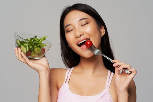 Donna tailandese felice che mangia insalata e pomodori
