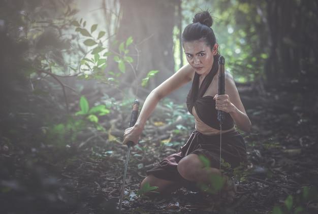 Donna tailandese in vestito militare antico della tailandia e spade della tenuta della mano pronte a combattere.