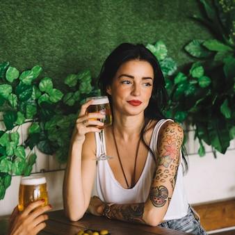 Donna tatuaggio che tiene una birra