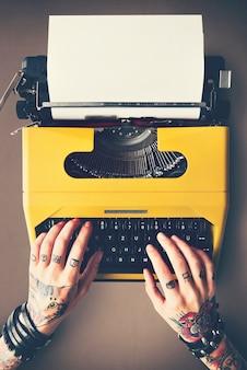 Donna tatuata che scrive su una macchina da scrivere d'annata