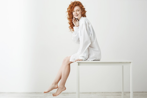 Donna tenera allegra con i capelli rossi ricci che ride in posa seduta sul tavolo. copia spazio.