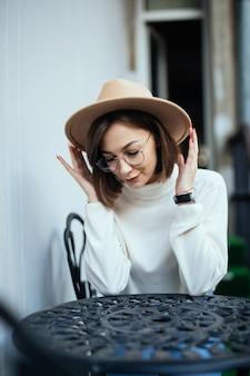 Donna tenera di moda di strada con manicure rosso e occhiali trasparenti seduto al tavolo