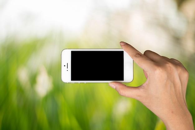 Donna tenere la mano e telefono astuto sulla luce del giorno con sfondo verde sfocato della natura.