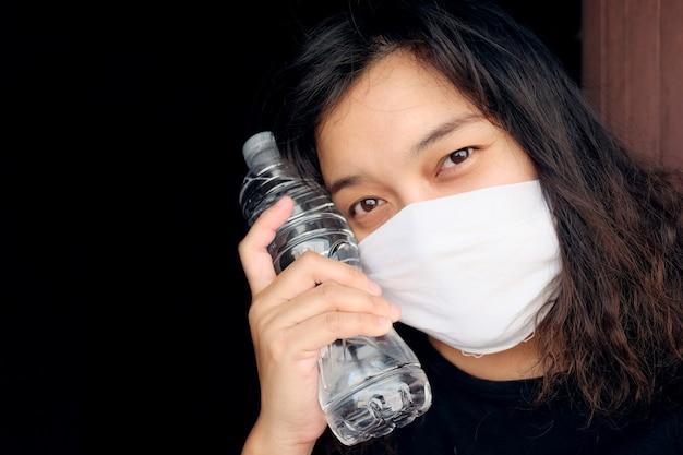 Donna thailandese asiatica che indossa una maschera di stoffa bianca per prevenire il virus covid-19 o corona e l'inquinamento atmosferico pm 2,5 in thailandia e mano che regge un'acqua minerale in bottiglia. concetto di salute e illnes