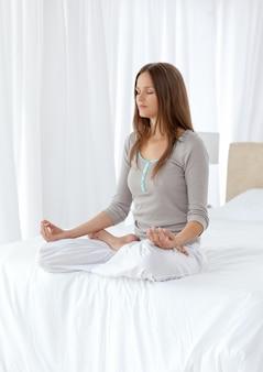 Donna tranquilla facendo esercizi di yoga sul letto