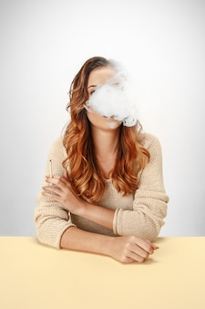 Donna tranquilla seduta e fumare a riposo al tavolo.
