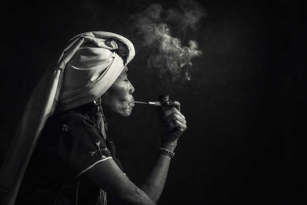Donna tribale di karen che fuma oppio con un tubo vicino a chiangmai, tailandia.