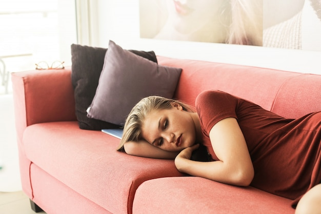 Donna triste bionda sdraiata su un divano