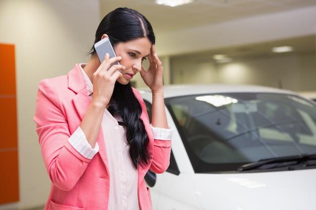 Donna triste che chiama qualcuno con il suo telefono cellulare