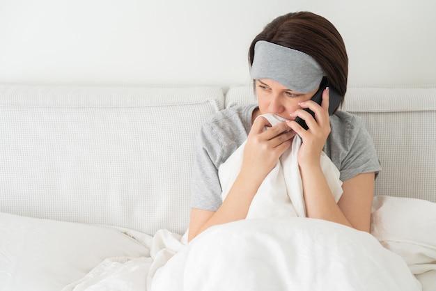 Donna triste che indossa la maschera per dormire utilizzando lo smartphone mentre si siede nel letto coperto di piumone