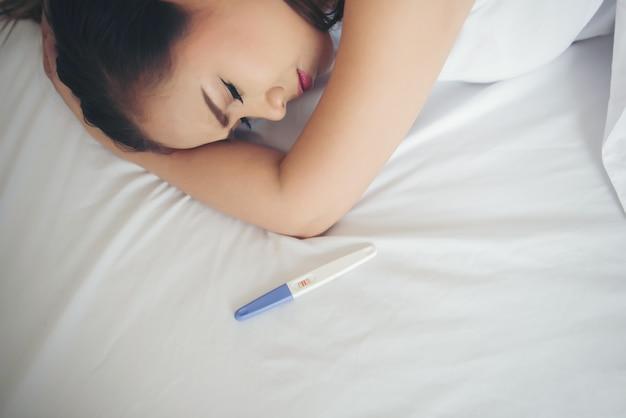 Donna triste che si lamenta tenendo un test di gravidanza che si siede sul letto