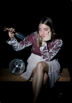 Donna triste che si siede con il bicchiere di champagne in mano