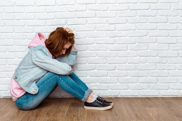 Donna triste che si siede sul pavimento vicino al muro