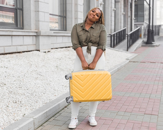 Donna triste che tiene i suoi bagagli gialli