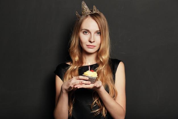 Donna triste, con una corona, in possesso di un cupcake compleanno