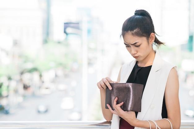 Donna triste guardando il suo portafoglio