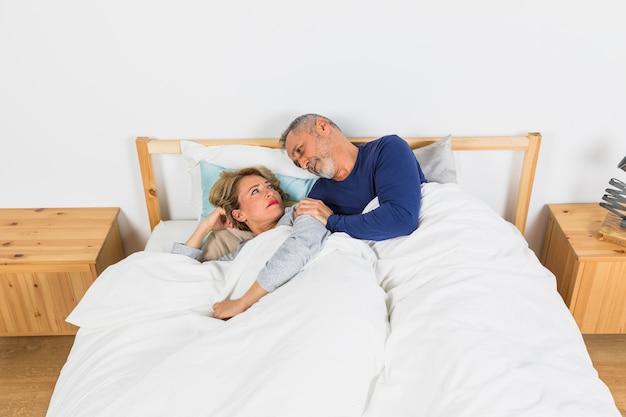 Donna triste invecchiata che si trova vicino all'uomo in piumino sul letto