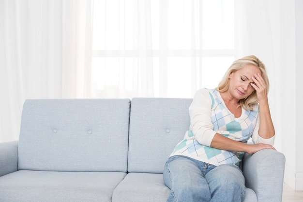 Donna turbata del colpo medio che si siede sul divano