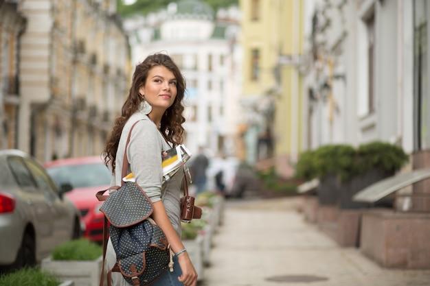 Donna turistica abbastanza giovane in vestiti casuali su un marciapiede della via.