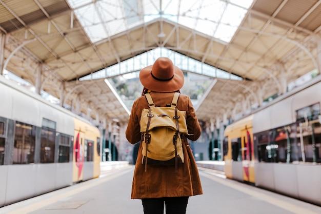 Donna turistica alla stazione ferroviaria. vista posteriore
