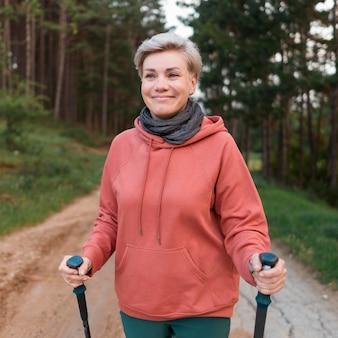 Donna turistica anziano felice nella foresta con bastoncini da trekking