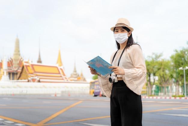Donna turistica asiatica che indossa una maschera protettiva
