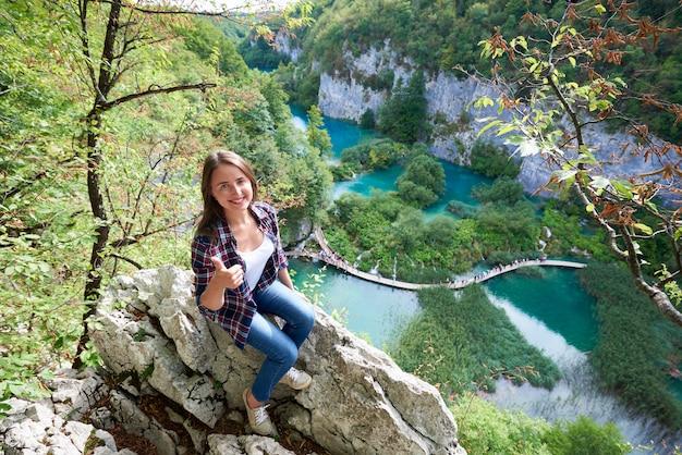 Donna turistica che mostra i pollici in su nei laghi plitvice