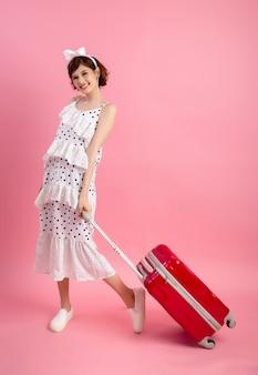 Donna turistica del viaggiatore in abbigliamento casual di estate con la valigia di viaggio isolata sul rosa