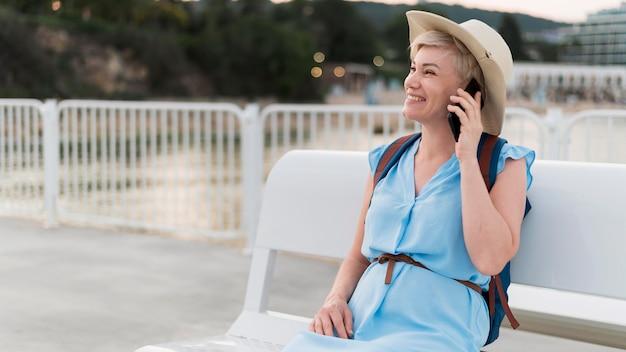 Donna turistica dell'anziano di smiley che comunica sul telefono