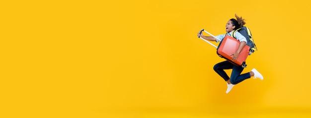 Donna turistica della donna afroamericana emozionante con il salto dei bagagli e dello zaino