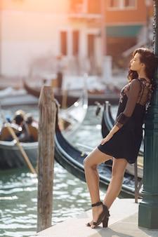 Donna turistica di viaggio sul molo contro la bella vista sul canale veneziano a venezia, italia.