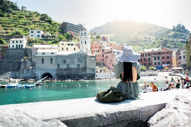 Donna turistica felice che esamina vista scenica di vecchio villaggio vernazza