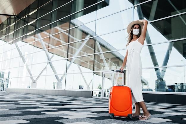Donna turistica in maschera madical in piedi con i bagagli vicino alla costruzione dell'aeroporto